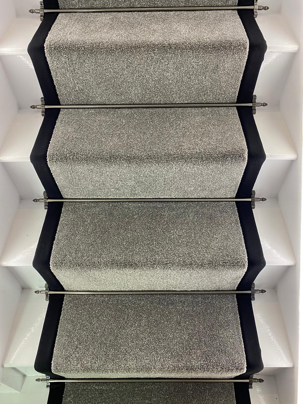 Carpet with bound edges to stairs with traditional stair rods