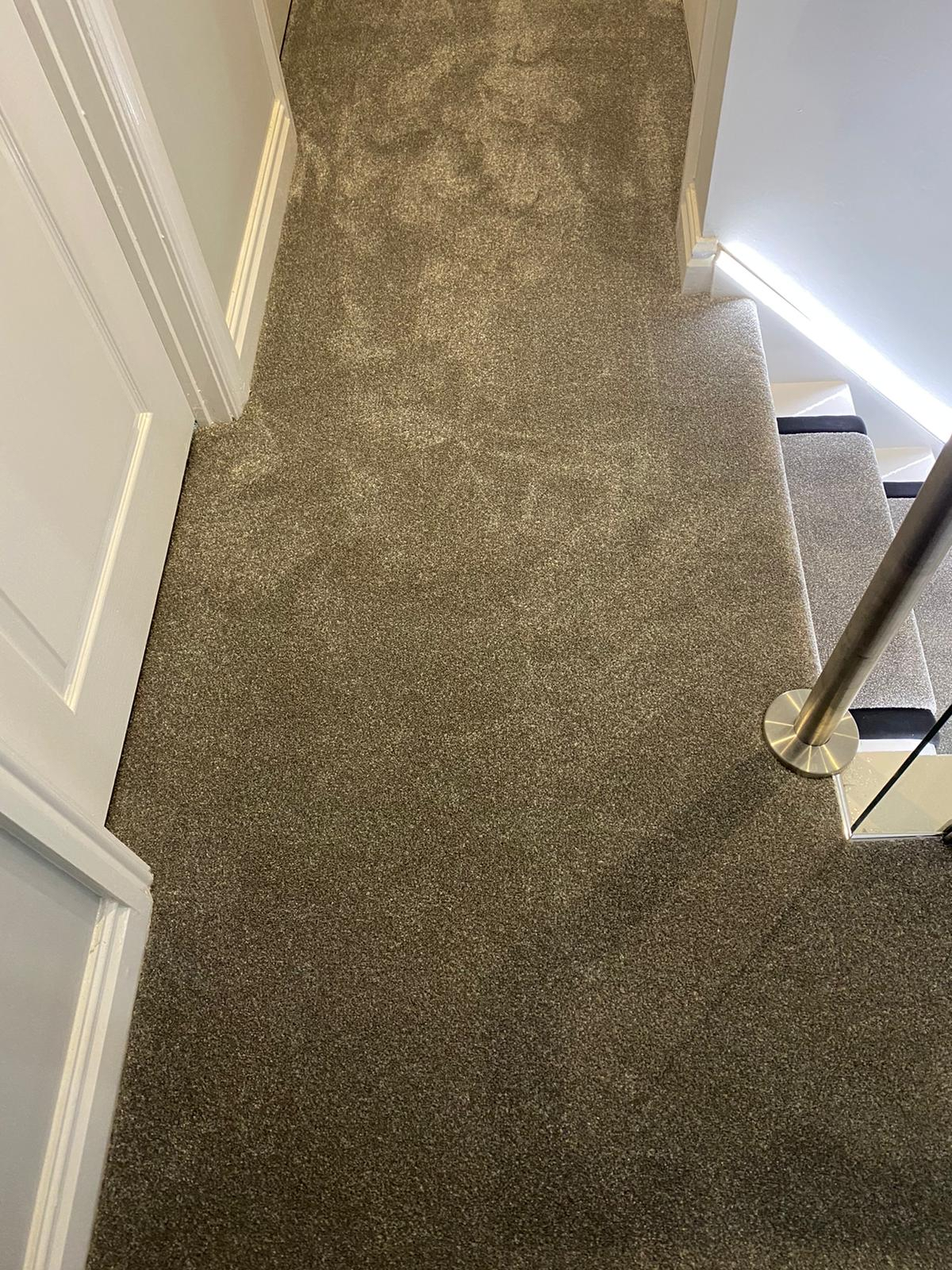 Luxury carpet to landing with bound edges to stairs