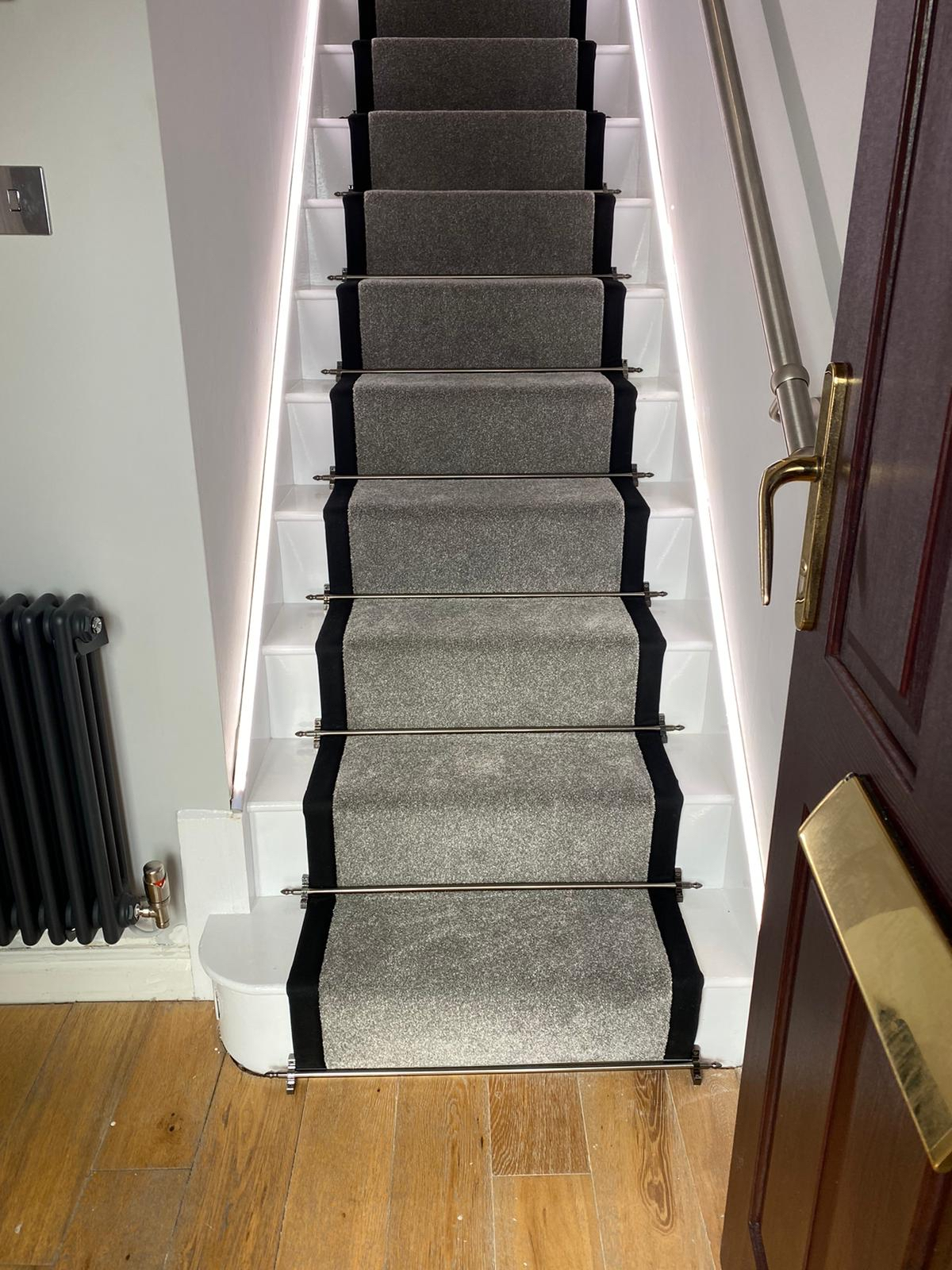 Luxury carpet to landing with bound edges to stairs and stair rods